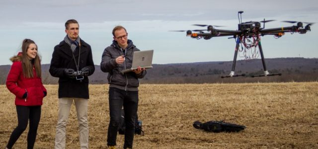 From left, Kerry Jones '19 (ENG), Ryan Heilemann '19 (ENG), and Josh Steil '19 (ENG) look on as their drone takes off for a test flight on Horsebarn Hill in Storrs. (Christopher Larosa/UConn Photo)